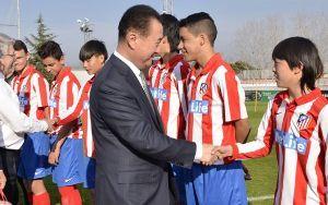 Wang Jianlin saluda a unos niños de la cantera del Atlético de Madrid