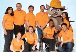 Los voluntarios (vistiendo la chomba de la discordia) con la mascota, Pachi el puercoespín.
